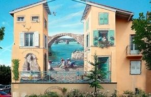 Роспись фасадов домов, выполненная французским художником, впечатляет своей реалистичностью